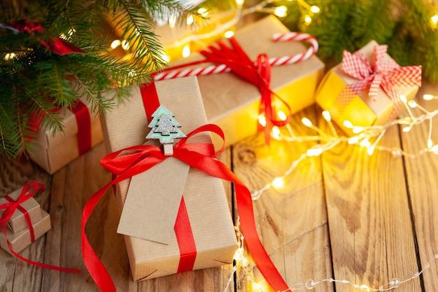 Des piles de cadeaux de noël posées sous un arbre de noël . coffrets cadeaux faits à la main. vacances de noël confortable, concept d'ambiance.