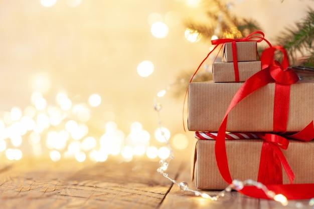 Des piles de cadeaux de noël posées sous un arbre de noël avec des lumières défocalisées. coffrets cadeaux faits à la main. vacances de noël confortable, concept d'ambiance.