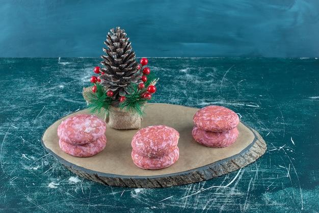 Des piles de cookies autour d'un ornement de noël sur une planche sur bleu.