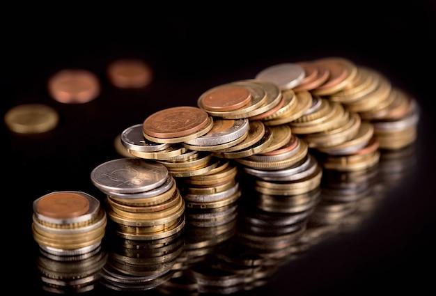 Piles de différentes pièces de pays cf sur fond noir.