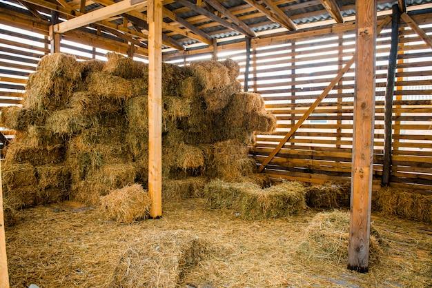 Piles de foin sec à l'intérieur d'une grange rurale en bois