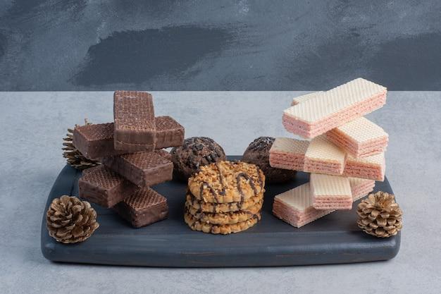 Des piles de gaufrettes et de biscuits sur une planche de la marine avec des pommes de pin sur la surface en marbre