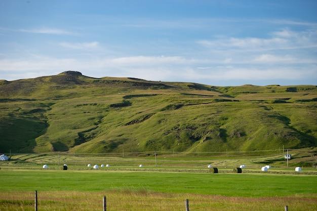 Des piles d'herbe sur un champ vert avec de belles collines verdoyantes et le ciel