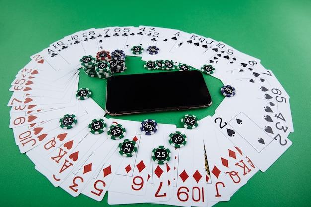 Des piles de jetons de poker et de cartes à jouer sur un ordinateur portable. concept de casino en ligne.