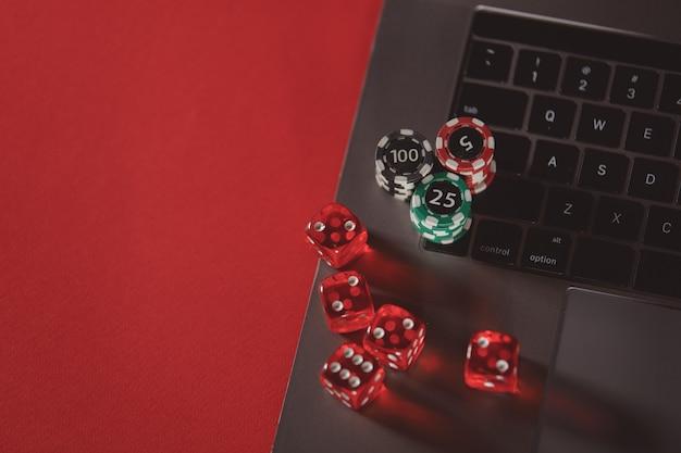 Des piles de dés de jetons de poker et un ordinateur portable sur un fond rouge concept en ligne de poker
