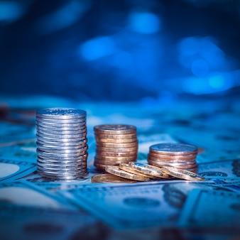 Des piles de pièces sur le fond des billets de cent dollars. lumière bleu foncé.
