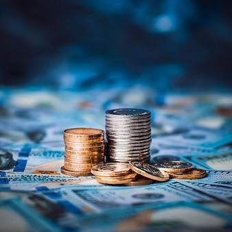 Des piles de pièces de monnaie de cent dollars sont dispersées dans tout l'espace. les pièces sont rassemblées en deux colonnes, elles sont brillantes, de couleur dorée.