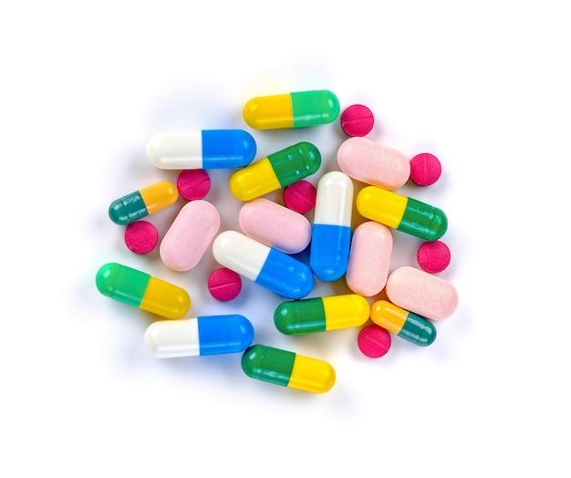 Des piles de pilules et capsule sur fond blanc
