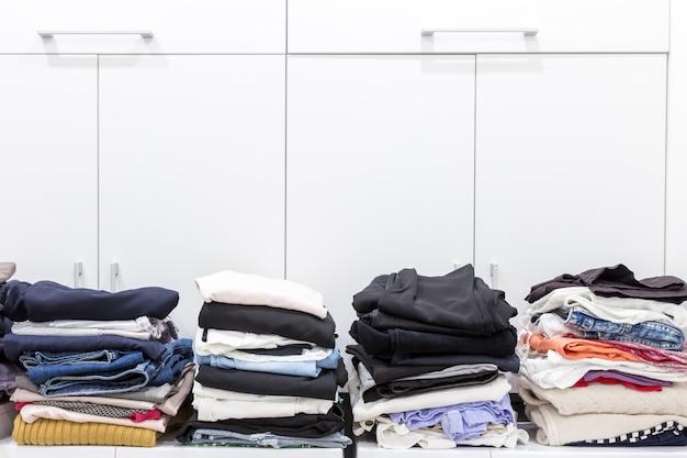 Des piles de vêtements propres dans une buanderie