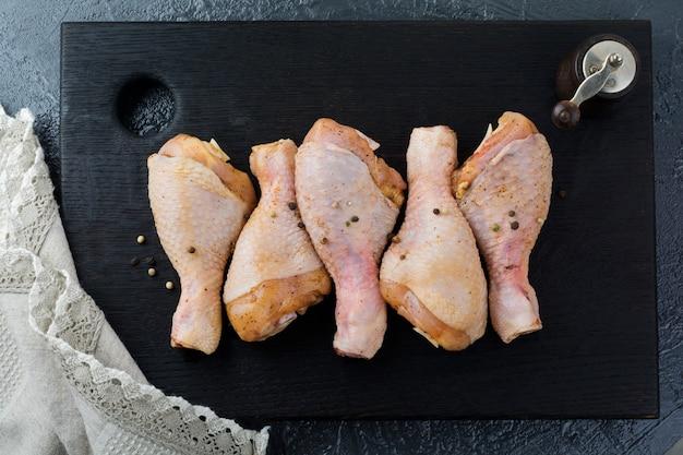 Pilon de poulet cru en marinade avec poivre, sauce soja, persil et oignon sur un support en bois noir