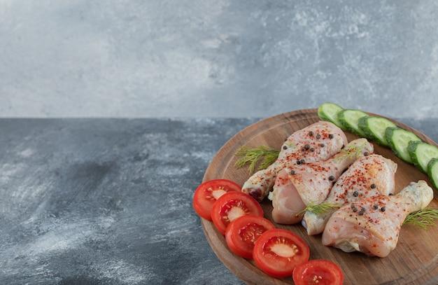 Pilon de poulet cru mariné sur planche de bois.