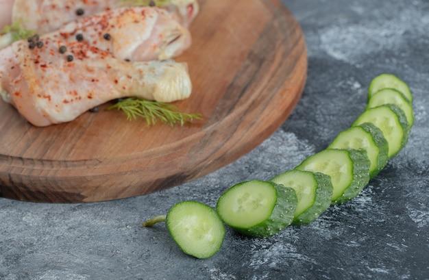 Pilon de poulet cru sur planche de bois et concombre frais en tranches.