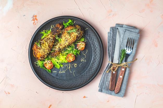 Pilon de poulet cuit au four dans une assiette en céramique noire