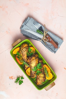 Pilon de poulet cuit au four dans un plat vert avec orange et romarin