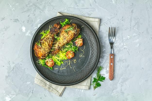 Pilon de poulet dans une assiette en céramique noire avec orange et romarin