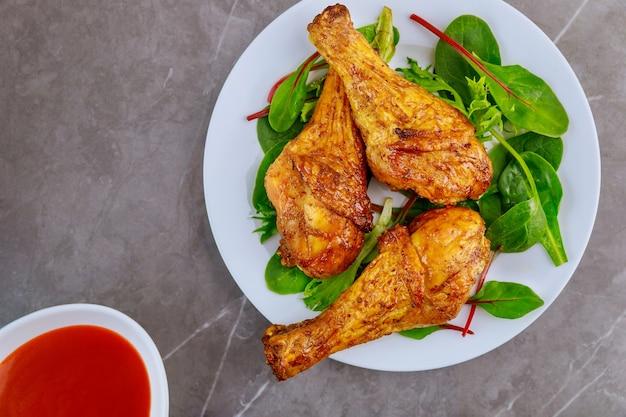 Pilon de poulet épicé rôti avec salade et sauce sur table grise. vue de dessus.
