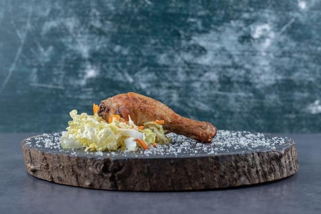 Pilon de poulet frit et salade sur morceau de bois.