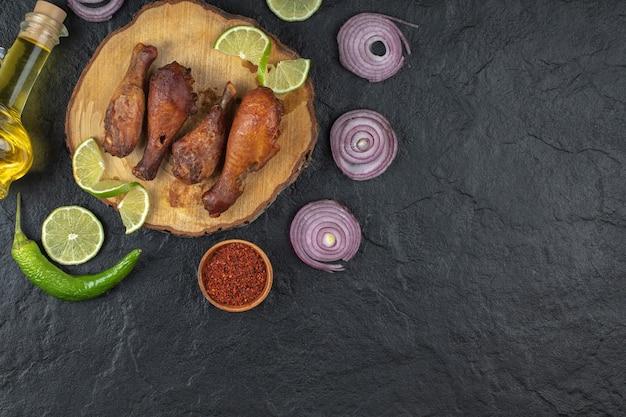 Pilon de poulet grillé avec des légumes sur la vue de dessus de planche de bois.