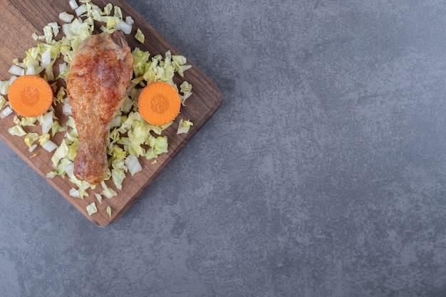 Pilon de poulet et légumes tranchés sur planche de bois.