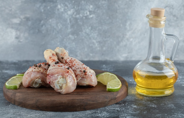 Pilon de poulet mariné frais avec de la chaux et de l'huile sur fond gris.