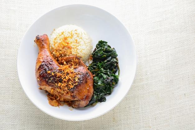 Pilon de poulet mariné avec une sauce au piment épicé et aux herbes, servi avec du riz cuit et des épinards.