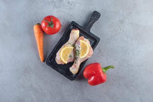 Pilons et citron tranché sur une planche à côté de légumes, sur la surface en marbre.