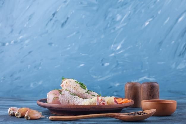 Pilons marinés et carottes en tranches sur une assiette en bois à côté d'épices, cuillère et ail sur la surface bleue