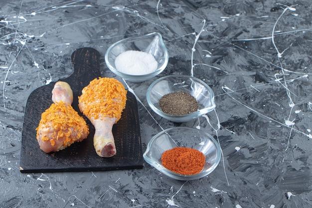 Pilons marinés sur une planche à découper à côté de bols à épices , sur fond de marbre.