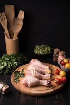 Pilons de poulet à angle élevé sur planche de bois avec des ingrédients
