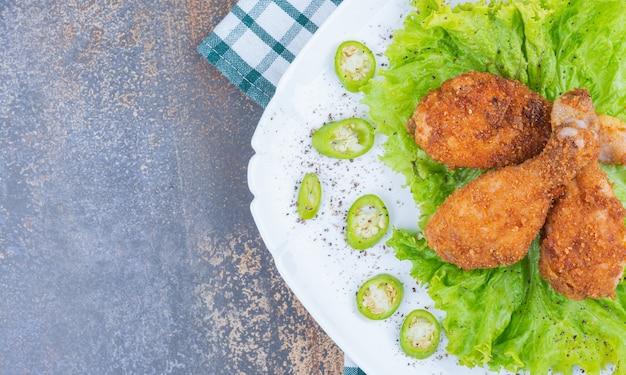 Pilons de poulet au four et légumes sur une assiette sur une serviette, sur le marbre.
