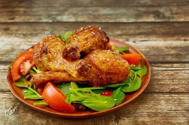 Pilons de poulet au four avec salade sur table en bois rustique, gros plan.