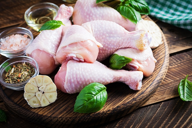 Pilons de poulet cru aux épices. cuisses de poulet cru aux épices sur une table en bois.
