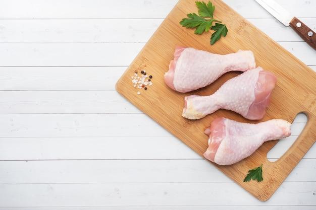 Pilons de poulet cru avec du persil et des épices sur une planche à découper en bois. espace copie vue de dessus