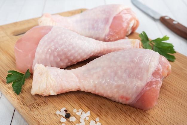 Pilons de poulet cru avec du persil et des épices sur une planche à découper en bois.
