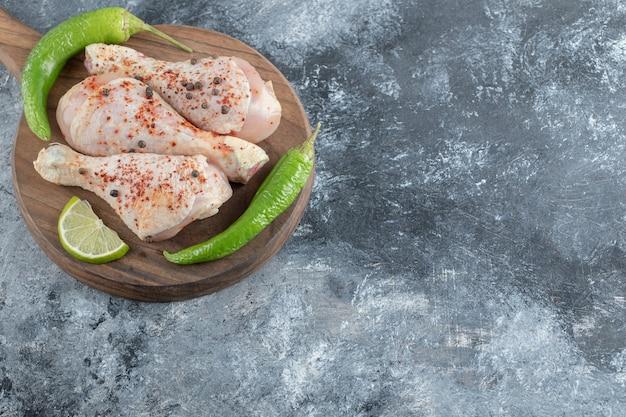 Pilons de poulet cru frais sur planche de bois.