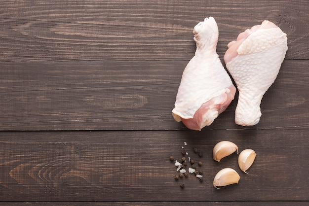 Pilons de poulet cru et poivre, sel, ail sur fond de bois