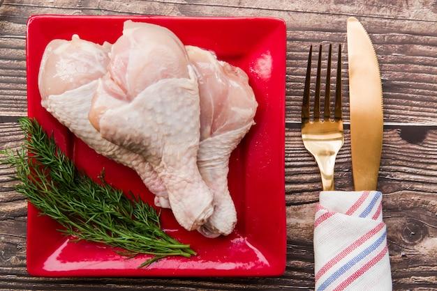Pilons de poulet crus à l'aneth frais dans une assiette avec une fourchette et un couteau à beurre