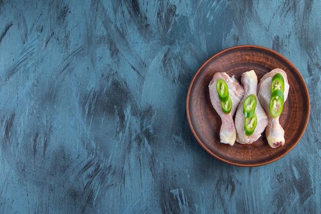 Pilons de poulet crus et poivrons tranchés sur une assiette, sur fond bleu.