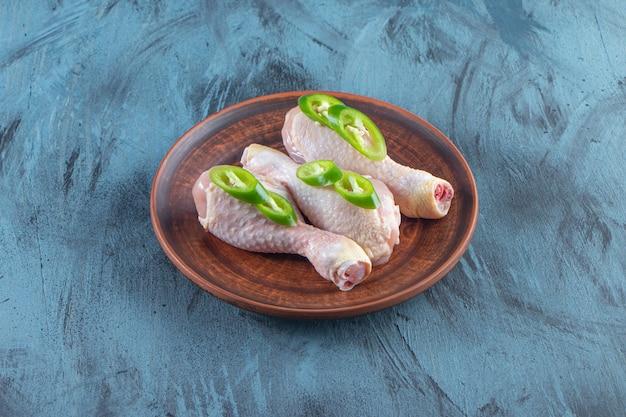 Pilons de poulet crus et poivrons tranchés sur une assiette, sur la surface bleue.