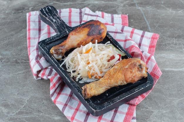 Pilons de poulet fraîchement grillés et choucroute sur planche de bois noir.