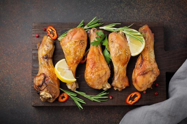 Pilons de poulet frit sur une planche à découper en bois sur une surface de béton ou de pierre sombre. mise au point sélective