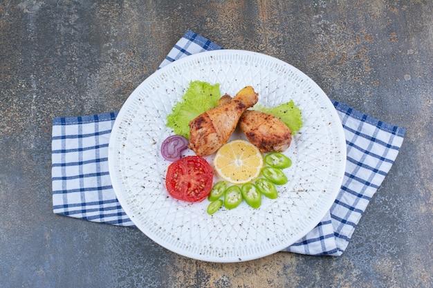 Pilons de poulet grillé sur plaque blanche avec des légumes.