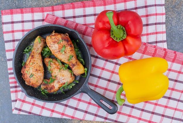 Pilons de poulet grillé sur la poêle avec des poivrons.