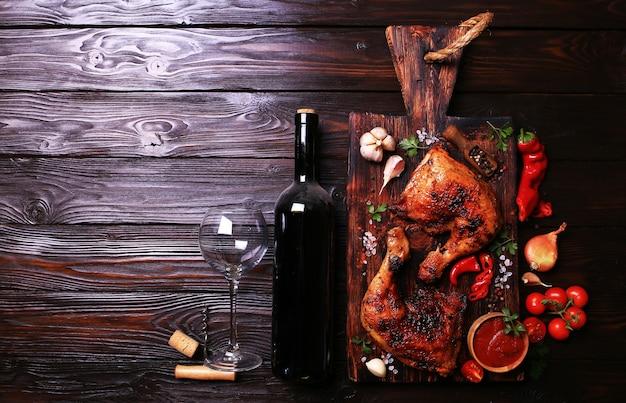 Pilons de poulet grillés aux épices et légumes, accompagnés d'une bouteille de vin rouge.