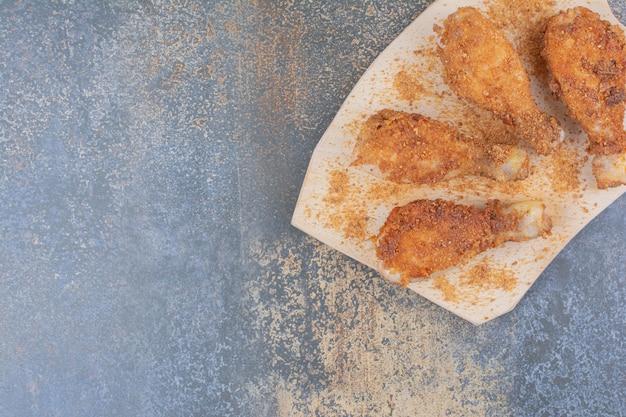 Pilons de poulet grillés sur planche de bois avec chapelure. photo de haute qualité