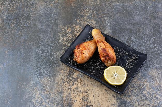 Pilons de poulet grillés sur plaque noire au citron. photo de haute qualité