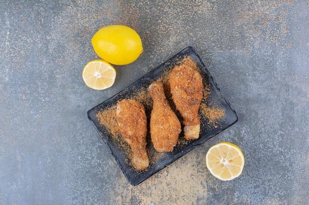 Pilons de poulet grillés sur plaque noire avec des citrons. photo de haute qualité