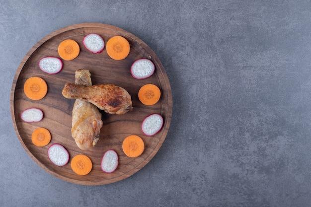 Pilons de poulet et légumes tranchés sur plaque de bois.