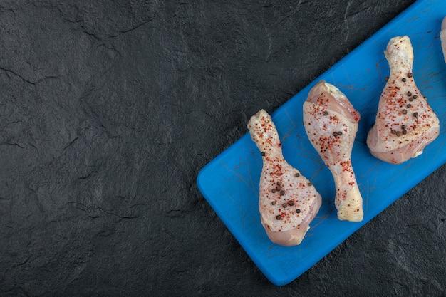 Pilons de poulet marinés sur planche de bois bleue.