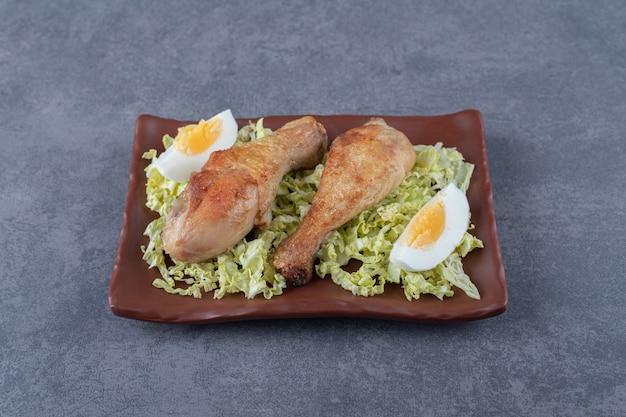 Pilons de poulet et œufs durs sur plaque brune.